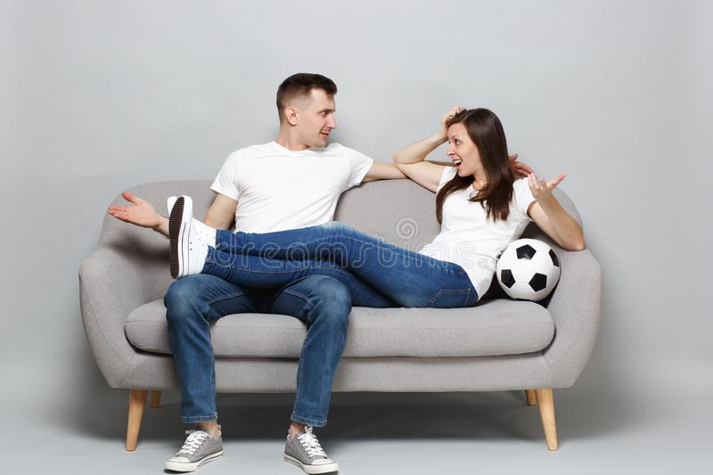 Nervous couple woman man football fans cheer up support favorite team with soccer ball spreading hands looking at each stock photos