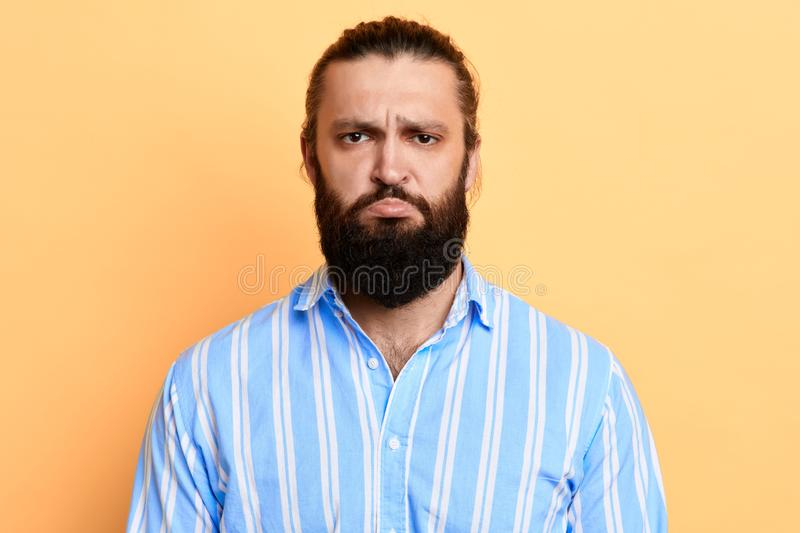 Nervous doubtful handsome bearded man frowning his eyebrows stock image