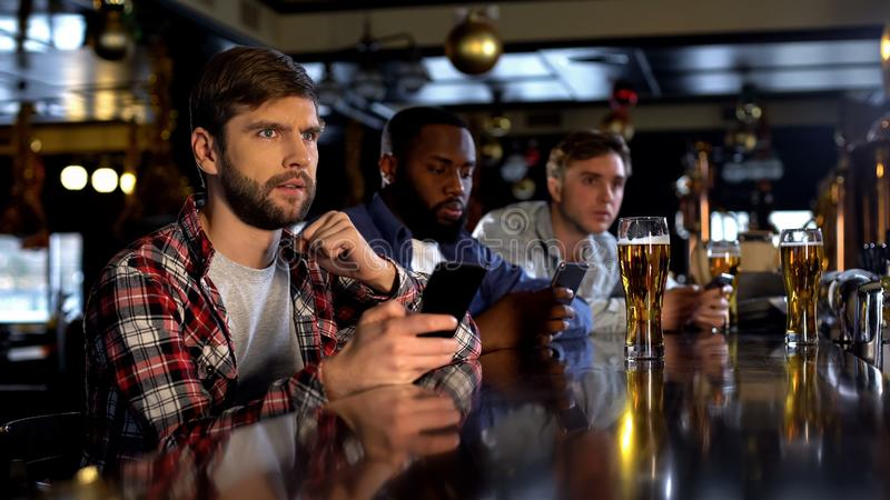 Nervous fans checking bets on smartphone, watching game in bar, bookmaker app. Stock photo stock photography