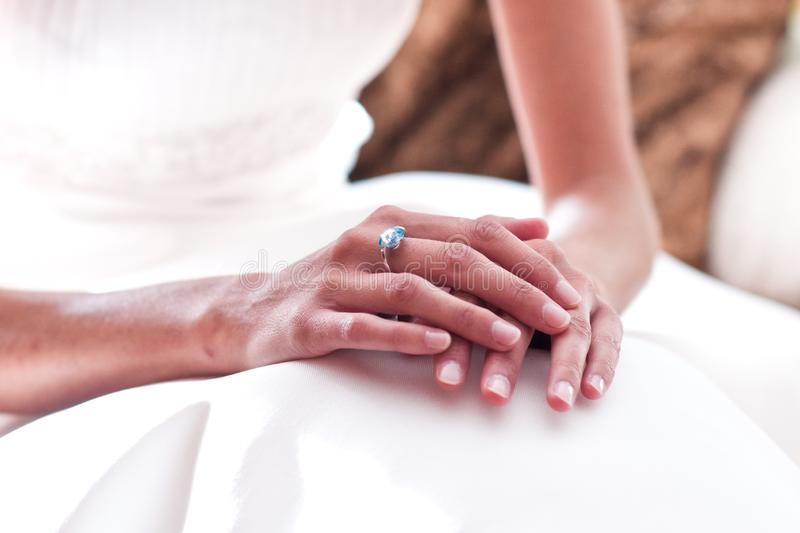 Nervous hands of a woman on her wedding day, with her white dress ready.  stock image