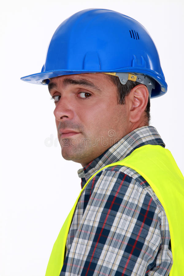 Nervous-looking tradesman. A nervous-looking tradesman covering away royalty free stock photos