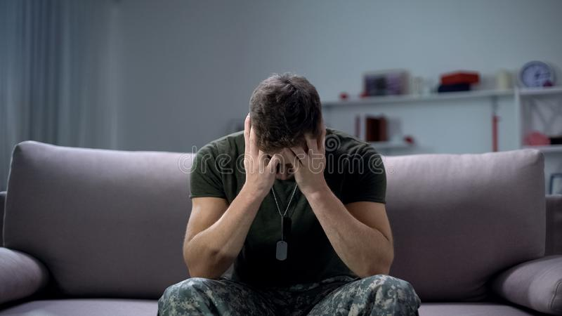 Nervous male military suffering depression, sitting alone at home, PTSD concept. Stock photo stock image