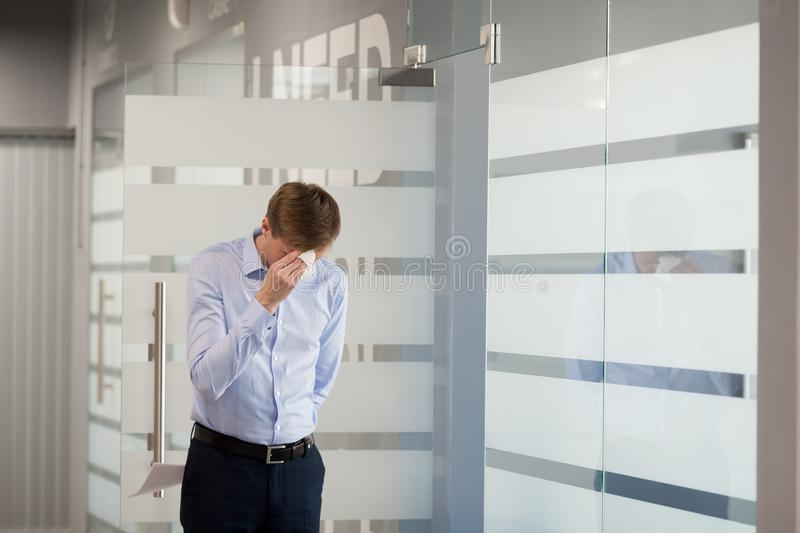 Nervous male worker stressed before making presentation in meeti. Nervous male employee wipe face sweating from worries before entering meeting room to make stock photography