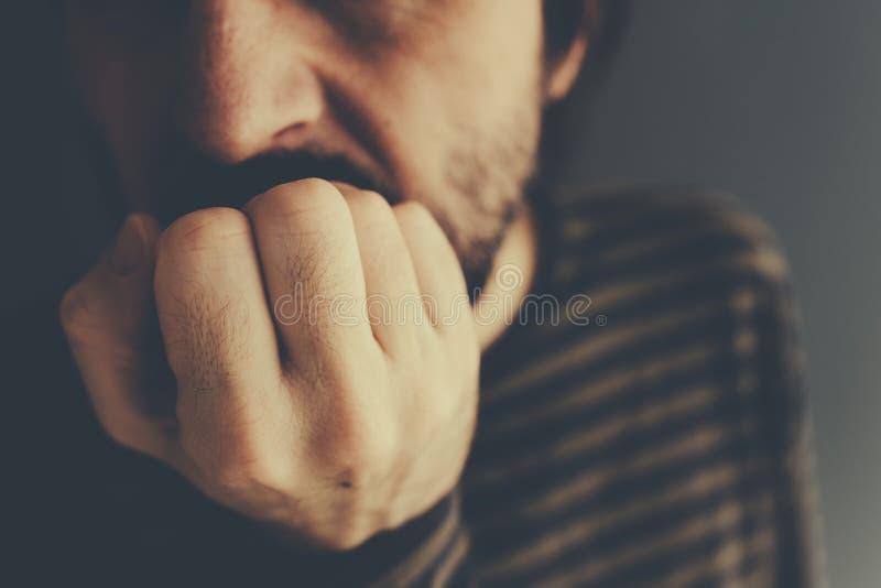 Nervous man bites fingernails stock photos