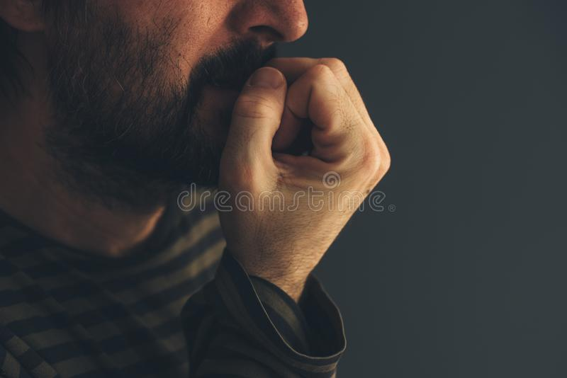 Nervous man bites fingernails stock photo