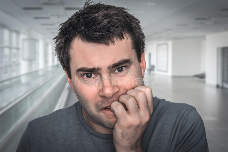 Nervous man biting his nails - nervous breakdown stock photography