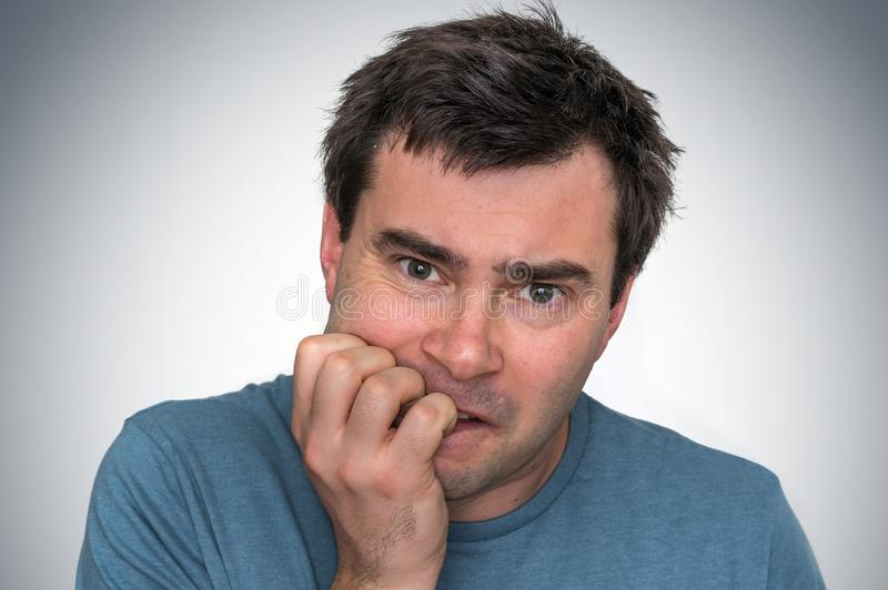 Nervous man biting his nails - nervous breakdown stock photo