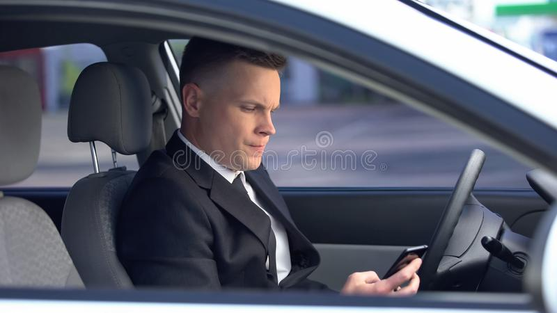 Nervous man in suit sitting on driver seat and calling on phone, late for work royalty free stock images