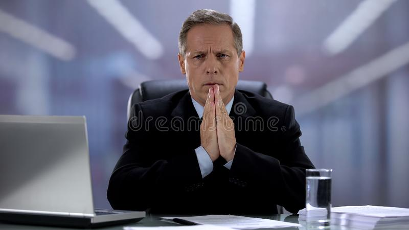 Nervous manager praying, waiting for important deal results, hoping for luck royalty free stock images