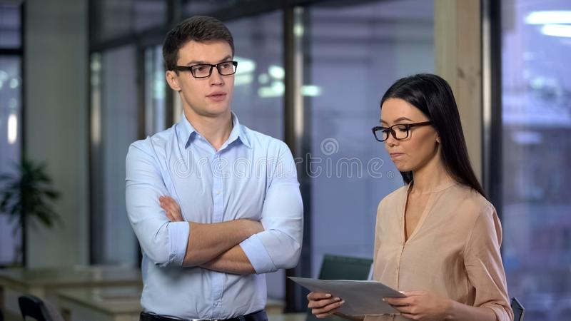 Nervous secretary holding documents feeling scared of male boss, office work stock images