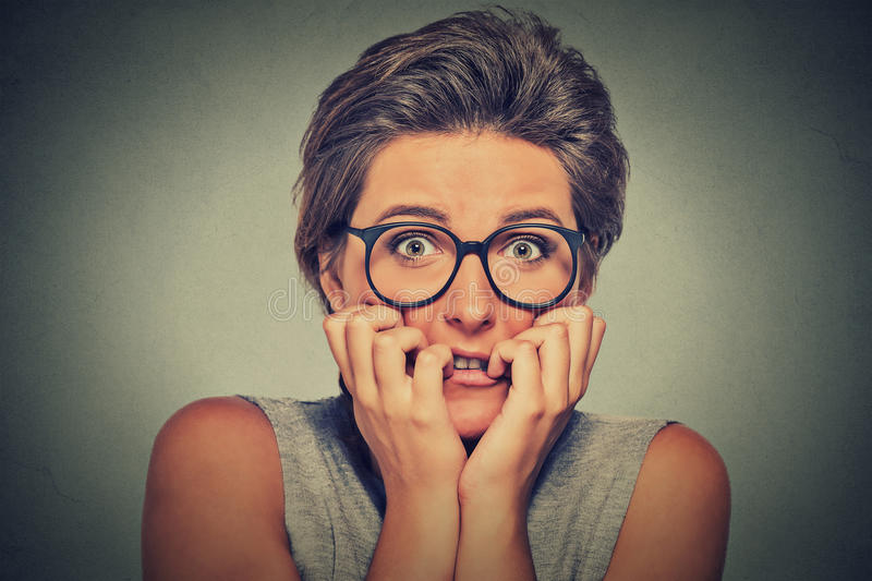 Nervous stressed anxious young woman with glasses girl biting fingernails. Headshot nervous stressed young woman with glasses girl biting fingernails looking royalty free stock photos