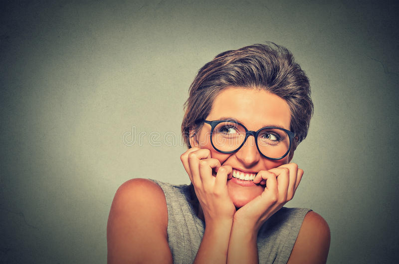 Nervous stressed anxious young woman with glasses girl biting fingernails. Headshot nervous stressed young woman with glasses girl biting fingernails looking stock image