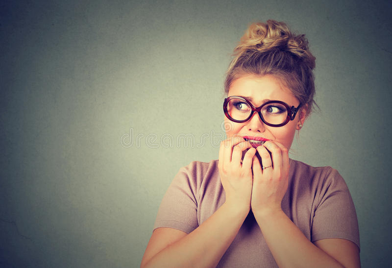 Nervous stressed young nerdy woman in glasses biting fingernails looking anxiously. Closeup portrait nervous stressed young nerdy woman in glasses biting royalty free stock image