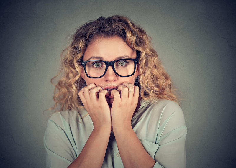 Nervous stressed young woman biting fingernails looking anxiously. Closeup portrait nervous stressed young woman biting fingernails looking anxiously craving royalty free stock image