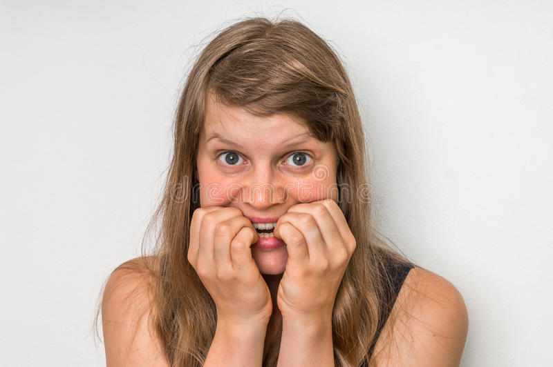 Nervous woman biting her nails stock photo