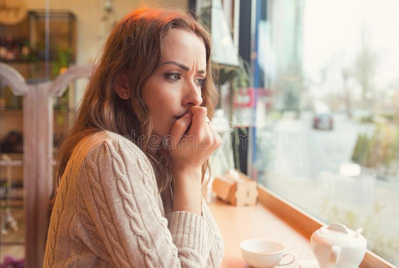 Nervous woman biting nails and looking away sitting alone in a coffee shop. Nervous worried young woman biting nails and looking away sitting alone in a coffee royalty free stock photo