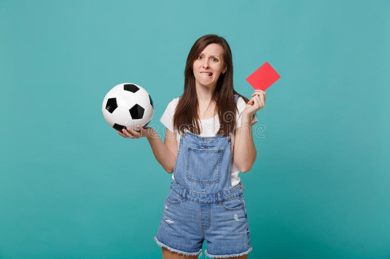 Nervous woman football fan support team with soccer ball, red card, biting lips, propose player retire from field. Isolated on blue turquoise background. People stock photos