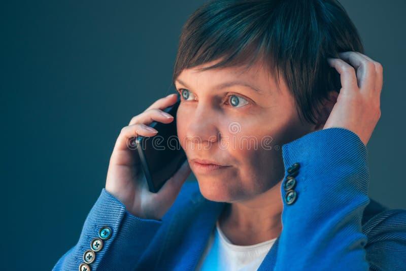 Nervous worried businesswoman during unpleasant telephone conversation stock photos
