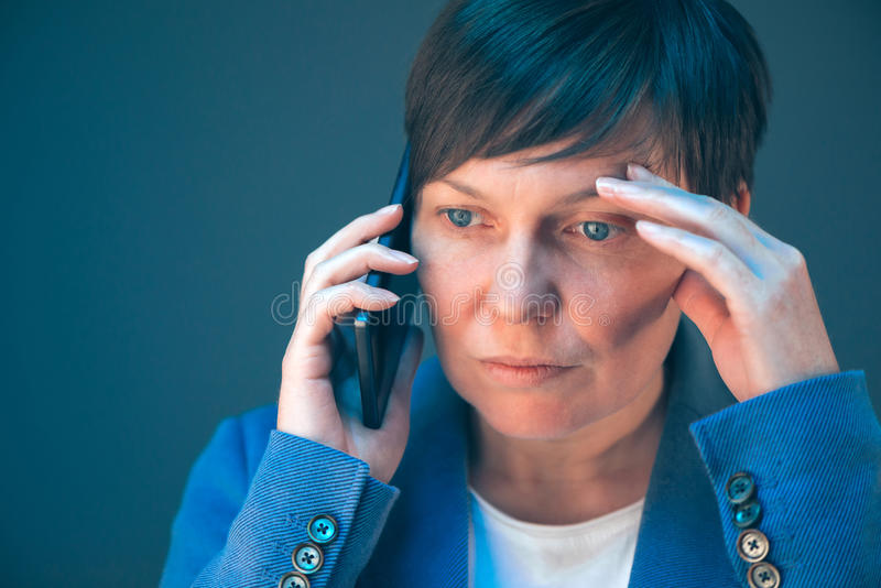 Nervous worried businesswoman during unpleasant telephone conversation royalty free stock images