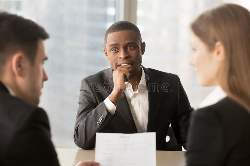 Nervous worried unhired african-american job applicant waiting f. Nervous worried unemployed african-american job applicant waiting for result while employers or stock images