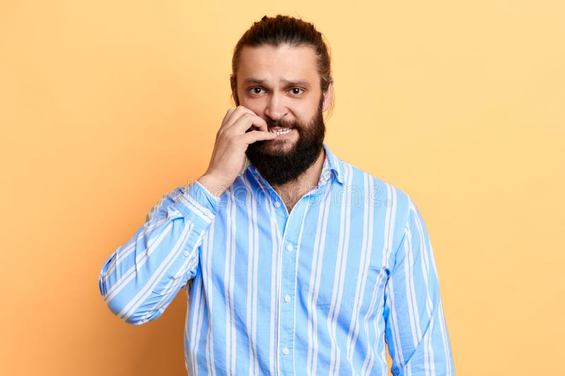 Nervous young man with worried expression biting his nails stock photos