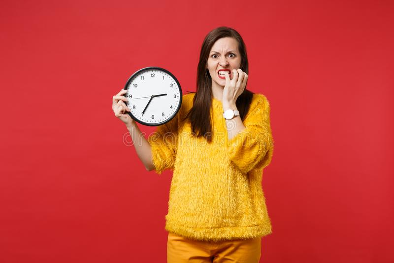 Nervous young woman in yellow fur sweater gnawing nails, holding round clock isolated on red background in studio. Time. Is running out. People sincere emotions royalty free stock image