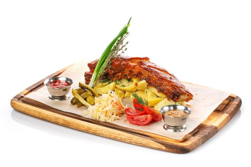 Nervure et Fried Potato de porc grillés délicieux avec de la sauce et des légumes sur la planche à découper en bois, photographie stock libre de droits
