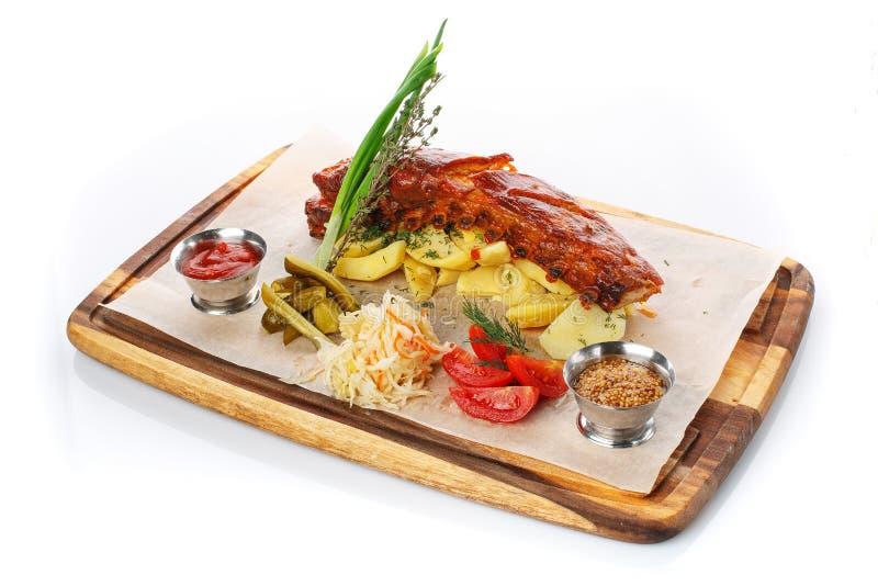 Nervure et Fried Potato de porc grillés délicieux avec de la sauce et des légumes sur la planche à découper en bois, photo stock