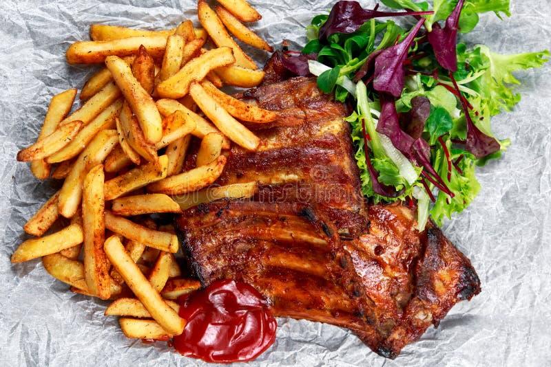 Nervure rôtie de porc, Fried Potato du plat blanc avec des légumes image libre de droits