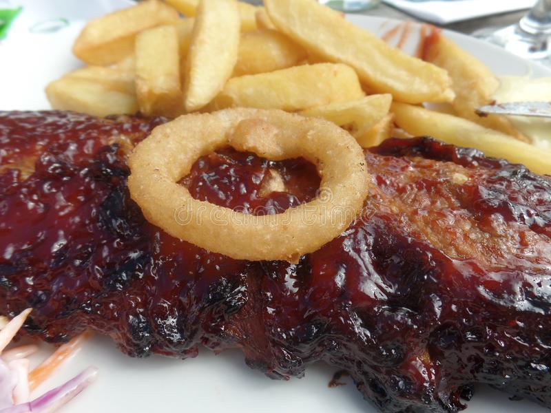 Nervures collantes de barbecue avec des anneaux de frites, de salade de choux et d'oignon photographie stock