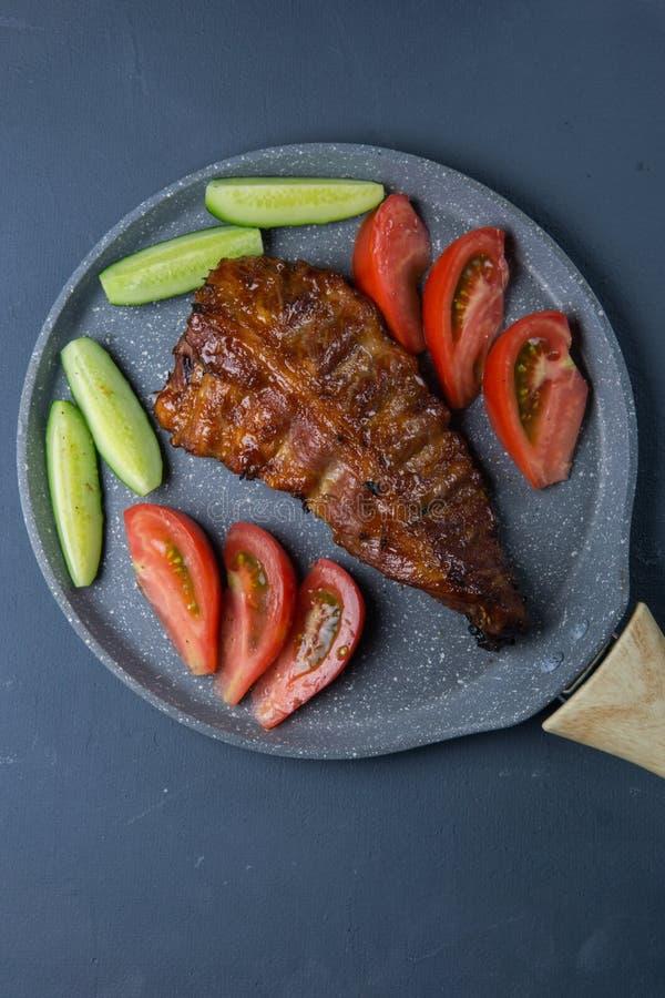 nervures de porc cuites au four avec le mensonge de miel avec les tomates et les concombres coupés en tranches frais de ‹d'†de  images libres de droits