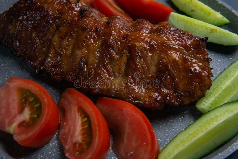 nervures de porc cuites au four avec le mensonge de miel avec les tomates et les concombres coupés en tranches frais de ‹d'†de  image stock