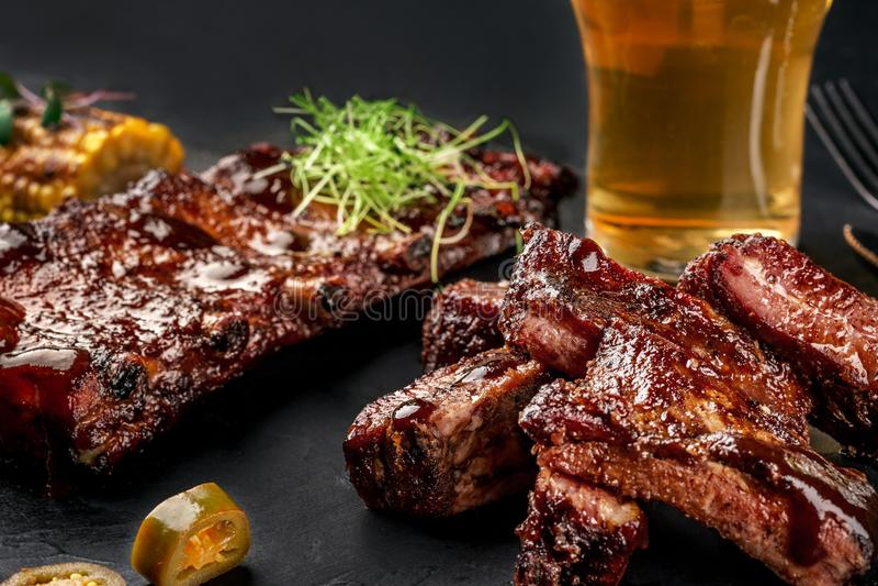 Nervures de porc dans la sauce barbecue et un verre de bière sur un plat noir d'ardoise Un grand casse-croûte à la bière sur un f image stock
