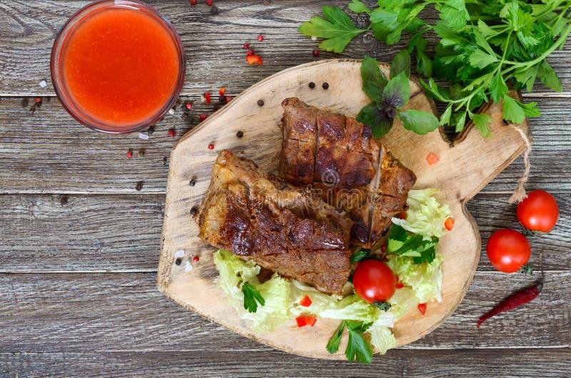 Nervures de porc frites avec des verts sur une planche à découper image stock