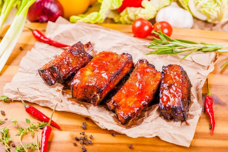 Nervures de porc grillées de barbecue avec des épices et des herbes sur le conseil en bois photographie stock libre de droits