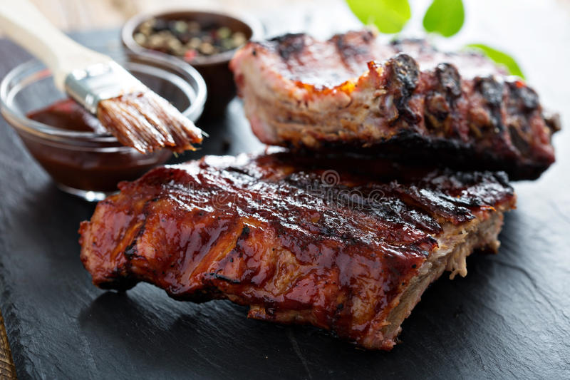 Nervures grillées de bébé de porc avec de la sauce à BBQ photographie stock