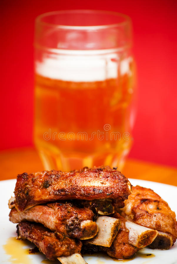 Nervures rôties de porc d'un plat blanc avec un broc de bière image libre de droits