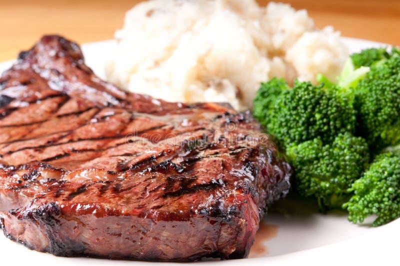 Nervurez le bifteck avec les potatooes et le brocolli écrasés par ail images libres de droits