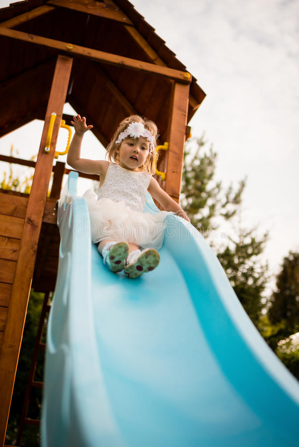 Nerwowa dziecka dziecka dziewczyna ślizga się w dół huśtawkę zdjęcia stock