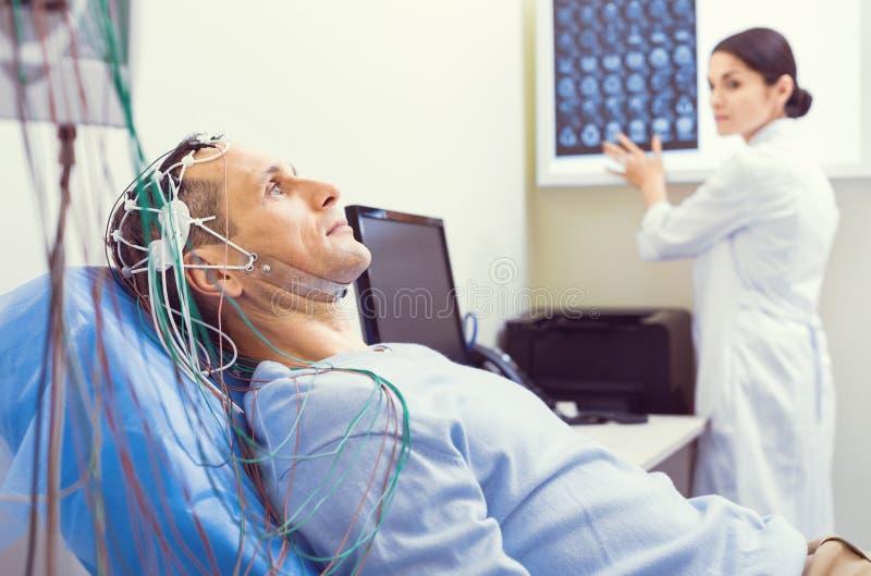 Nerwowy dżentelmen dostaje mózg analizujący electroencephalography maszyną zdjęcia royalty free