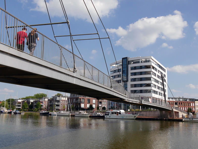 The Nesse bridge in Leer, Germany. Couple cross the Nesse Bridge in Leer, Germany, The bridge connects the historic city center with the pedestrian zone and royalty free stock photos
