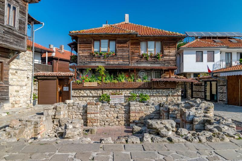 Nessebar, Bulgaria - 7 Sep 2018: Ancient ruins and a beautiful wooden house on a sunny day with blue sky in Nesebar ancient city. stock photography