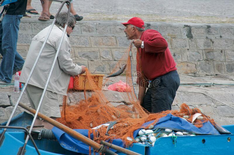 Nessebar, Bulgaria - September, 07, 2012: two elderly Bulgarian fishermen moored ashore with a fresh catch for trade. On the pier royalty free stock images