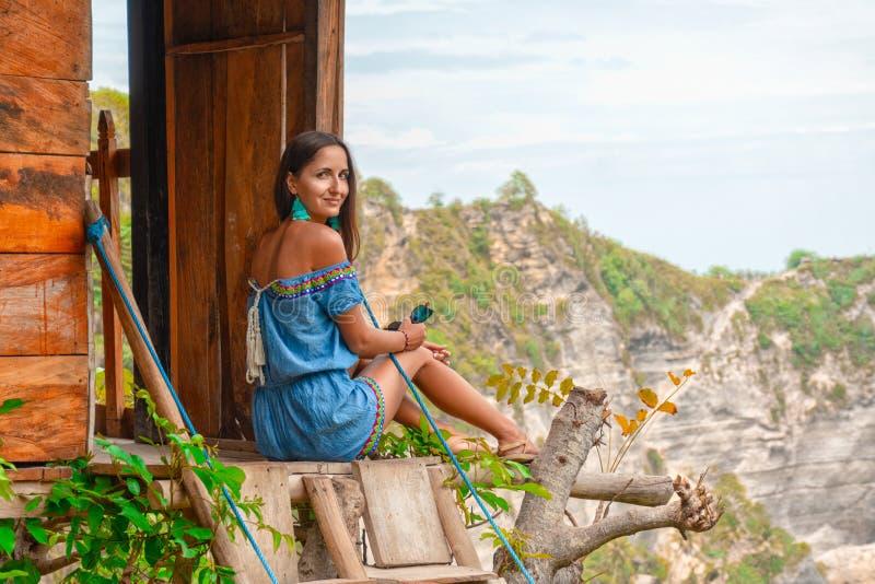 Nessun cure e nessun'attivit? Bella giovane donna in swimwear che si rilassa mentre sedendosi nella casa sull'albero all'aperto immagine stock