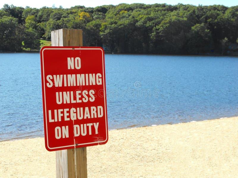 Nessun nuoto a meno che segno in servizio della spiaggia del bagnino immagine stock