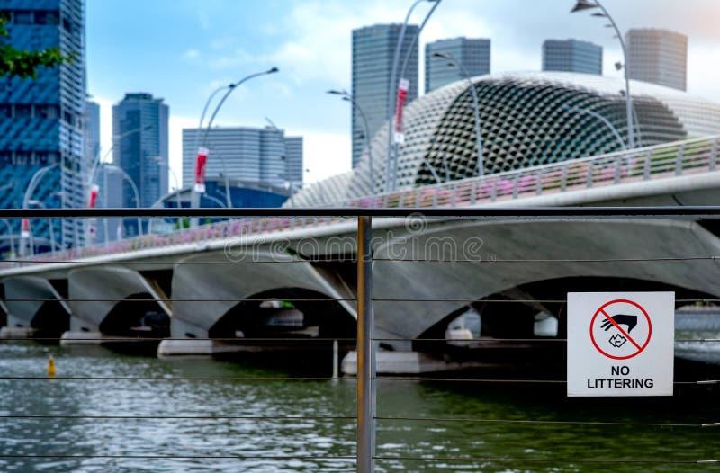 Nessun segno di figliata sul recinto di filo metallico accanto al fiume in città con la costruzione di affari del grattacielo Seg fotografia stock