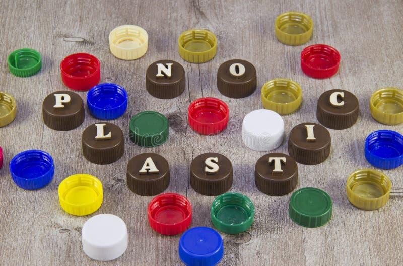 nessuna plastica Iscrizioni nelle lettere di legno sui tappi di bottiglia di plastica immagine stock