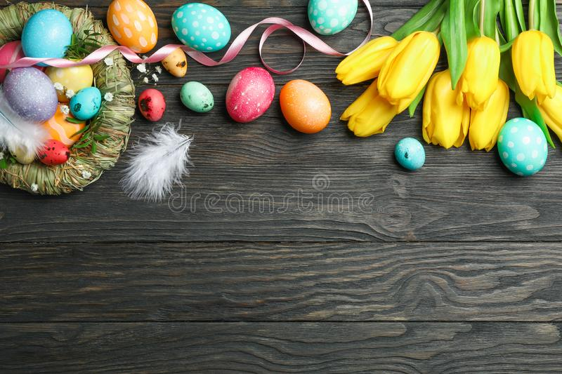 Nest with сolorful easter eggs, flowers and feathers on wooden background. Festive tradition. Space for text stock images