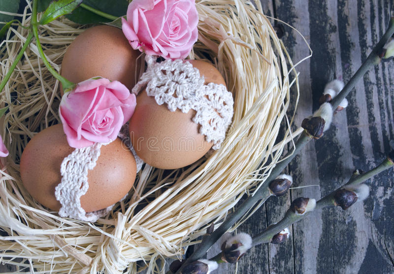 Nest with decorated eggs, roses and willow twigs on vintage wooden background. Spring Easter holiday arrangement royalty free stock photos