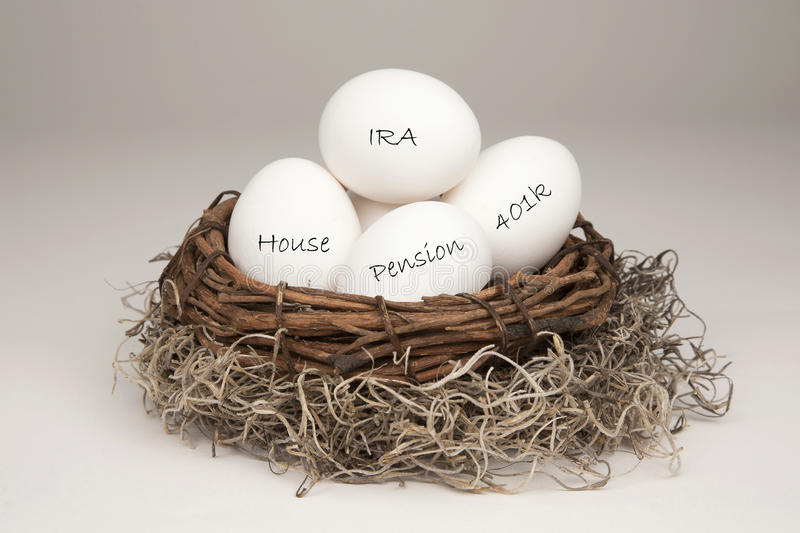 Nest Egg White. White eggs in a brown nest labelled with IRA, Pension, 401k and House representing a typical nest egg royalty free stock image